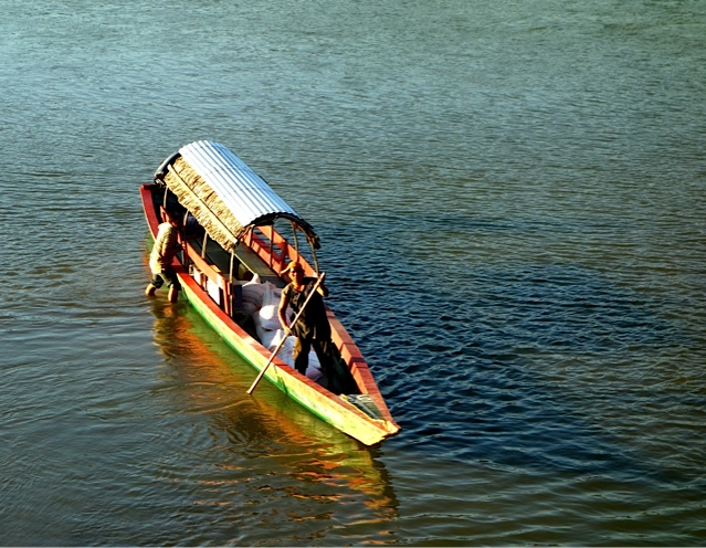 Riverboat being loaded in shallow water with cargo.
