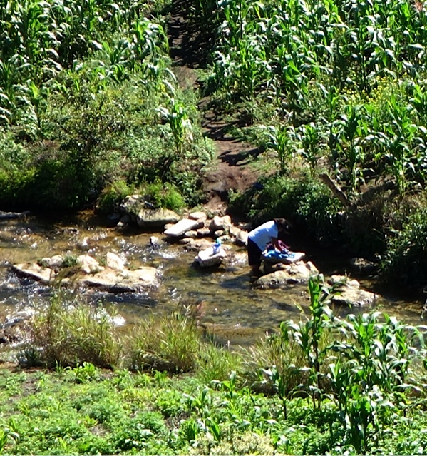 Far below us a woman washes clothes in the stream